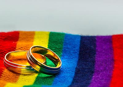 Two gold rings resting on a fabric surface in the colours of the LGBTQI+ flag